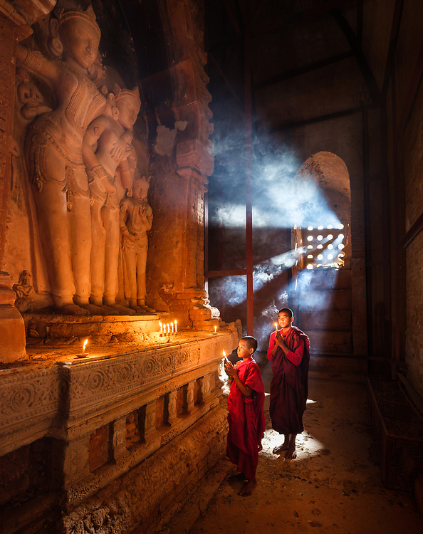 BAGAN, MYANMAR - CIRCA DECEMBER 2017: Monks inside a temple with candlelights praying.
