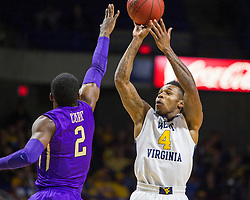 Nov 16, 2015; Charleston, WV, USA; West Virginia Mountaineers guard Daxter Miles Jr. shoots a three pointer over James Madison Dukes guard Ron Curry during the first half at the Charleston Civic Center. Mandatory Credit: Ben Queen-USA TODAY Sports