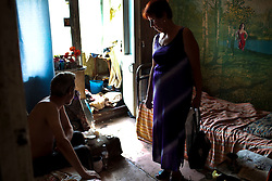 Ivan Cailiye, a patient with TB, sits in his home, which is filled with trash. Ivan is unemployed and has  leg injury, making it difficult for him to get to the hospital to take his treatment.  He relies on a local NGO to bring him his daily medicine.