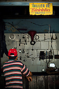 A man waits at the counter of a bicycle workshop in Baracoa, Cuba on Monday July 14, 2008.