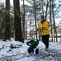 Russell Johnson, of Tupelo, uses a seed spreader to spread salt onto his steed driveway on Rachel Street in the Oakcliff Villas neighborhood in east Tupelo to try and speed up the process of melting the ice so his wife will be able to leave for work later in the day.