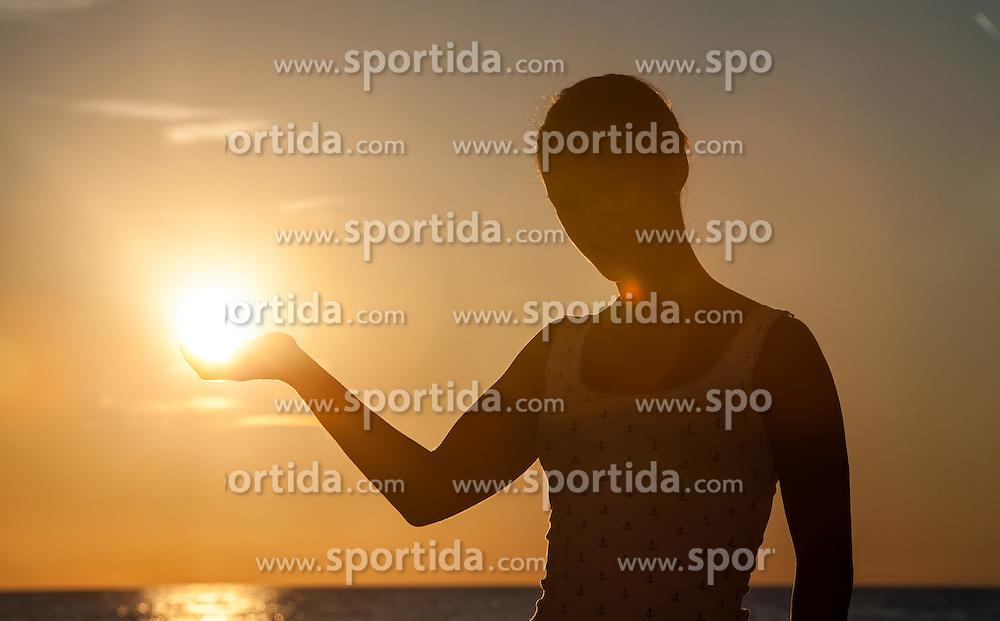 THEMENBILD - URLAUB IN KROATIEN, eine junge Frau hält mit ihrer Hand die Sonne in der Abendstimmung, aufgenommen am 03.07.2014 in Porec, Kroatien // a young woman holds with her hand the sun in the evening atmosphere at Porec, Croatia on 2014/07/03. EXPA Pictures © 2014, PhotoCredit: EXPA/ JFK