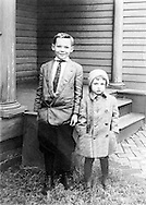 Brother and sister standing for portrait in the 1920s.
