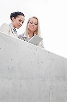 Low angle view of young businesswomen using digital tablet together while standing on terrace against sky