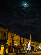 16 NOVEMBER 2016 - GEORGE TOWN, PENANG, MALAYSIA: A nearly full moon over a block of traditional colonial style shophouses in George Town, Penang.      PHOTO BY JACK KURTZ