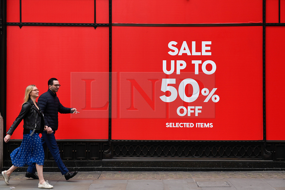 © Licensed to London News Pictures. 19/06/2019. LONDON, UK.  A couple passes by a retail store on Regent Street as the Summer Sales season begins, with many stores offering large discounts to clear inventories.  As retailers continue to face the threat of online shopping, some well known high street store chains have proposed company voluntary arrangements (CVA) to try to reduce high fixed rental property costs.  Photo credit: Stephen Chung/LNP