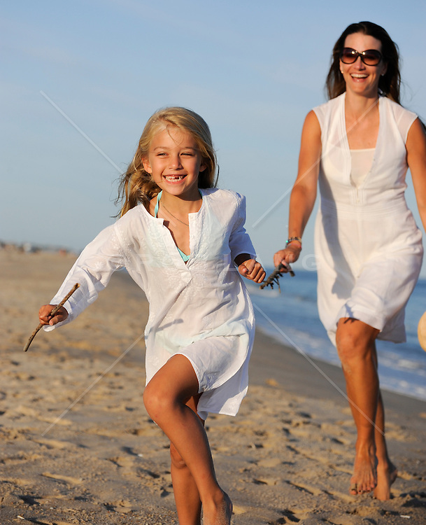 mother and young daughter running on the beach together in The Hamptons