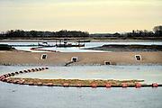 Nederland, Nijmegen, 23-11-2015 De nevengeul aan de overkant van de Waal bij Lent nadert zijn voltooiing. Laatste werkzaamheden. In de nieuwe dijk is een drempel gebouwd die stapsgewijs water doorlaat en bij hoogwater overloopt. Zicht op de inlaat, de drempel waar de geul begint. Grootste onderdeel van de vele werken van Rijkswaterstaat om bij hoogwater een betere waterafvoer in de rivier te hebben. Het is een omvangrijk project waarbij onder meer de pijlers van het spoorviaduct een bredere basis kregen omdat die straks in de loop van het water staan. Ook de n325 die vanaf de Waalbrug naar Arnhem loopt is over 400 meter opnieuw aangelegd omdat het talud vervangen wordt door een nieuwe brug met drie gracieuze pijlers. Het dorp veurlent komt op een kunstmatig eiland te liggen met twee bruggen als ontsluiting. Een voetgangersbrug en een andere, de Promenadebrug, voor normaal verkeer. Inmiddels begint de nieuwe kade aan de noordkant van deze geul vorm te krijgen. Ruimte voor de rivier, water, waal.The Netherlands, Nijmegen Measures taken by Nijmegen to give the river Waal, Rhine, more space to flow during highwater and to prevent the risk of flooding. Room for the river. Reducing the level, waterlevel. Large project to create a new paralel gully, an extra flow of water, so the river can drain more water during highwater. Due to climate change and expected rise, increase of the sealevel, the Dutch continue to protect their land from the water. Foto: Flip Franssen