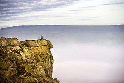 © Licensed to London News Pictures. 12/12/2016. Ilkley UK. A walker stands on top of the cow & calf rocks 1,319 ft above the fog covered town of Ilkley in Yorkshire this morning. Photo credit: Andrew McCaren/LNP