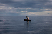 A fisherman is rowing on his boat near the island of Sao Tome, Sao Tome and Principe, (STP) a former Portuguese colony in the Gulf of Guinea, West Africa.