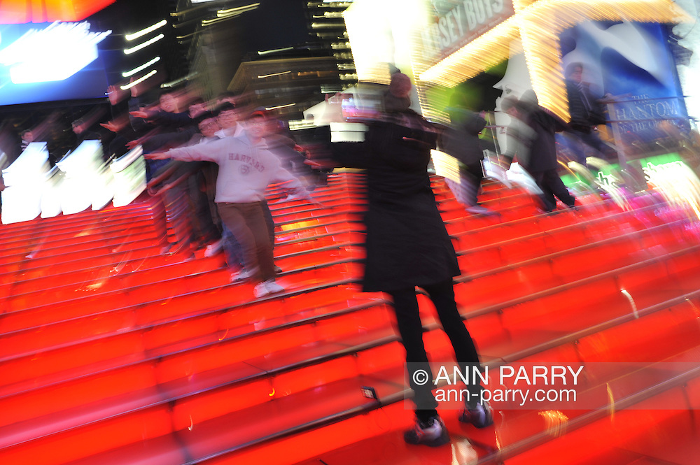 Group of college friends having fun on big TKTS Red Stairway at Times Square Duffy Square in Manhattan, New York, USA, night of  January 9, 2012