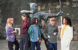 Multiracial group of teenagers standing near Robin Hood statue in grounds of Nottingham castle talking,