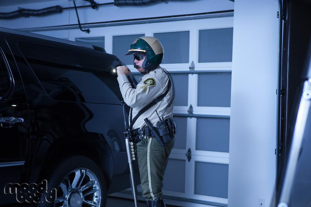 Nightwatch patrolman checks luxury car in garage