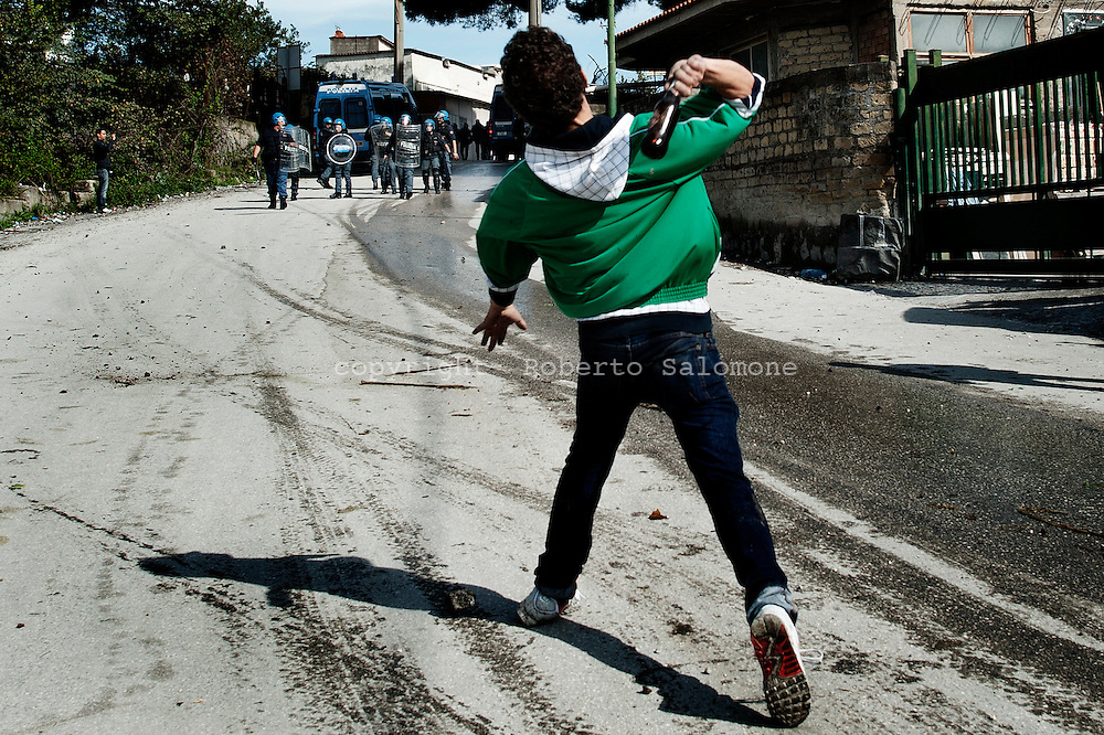 ITALY, Terzigno : A demonstrator throws a glass bottle against police in Terzigno on October 18, 2010. Demonstrators protest against the opening of a new dump on the slopes of Mount Vesuvius. AFP PHOTO / ROBERTO SALOMONE
