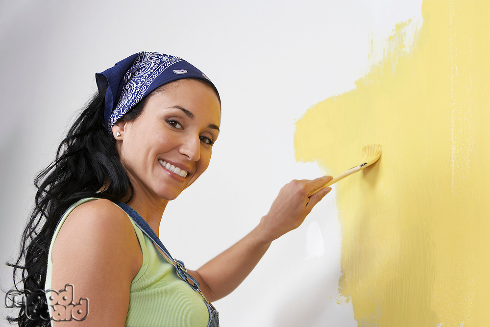 Woman painting interior wall low-angle view portrait