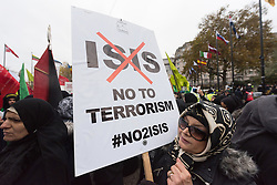 CAPTION CORRECTION © Licensed to London News Pictures. 20/11/2016. A woman carries a placard saying ISIS no to terrorism as she takes part in the annual Arbaeen procession,  which marks a sacred Shia Muslim ritual. Arbaeen, also known as Chehlum, commemorates the end of the 40-day mourning period after the killing of Imam Hussein, the Prophet Muhammad's grandson, in a battle in 680 AD. His martyrdom is considered a defining event in the schism between Sunni and Shia Muslims. London, UK. Photo credit: Ray Tang/LNP