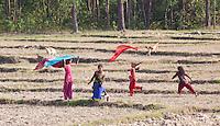 Children running and playing on farmland, Bardiya, Nepal