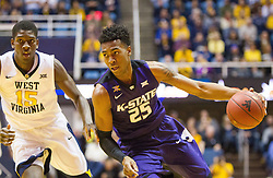 Feb 11, 2017; Morgantown, WV, USA; Kansas State Wildcats forward Wesley Iwundu (25) drives past West Virginia Mountaineers forward Lamont West (15) during the first half at WVU Coliseum. Mandatory Credit: Ben Queen-USA TODAY Sports