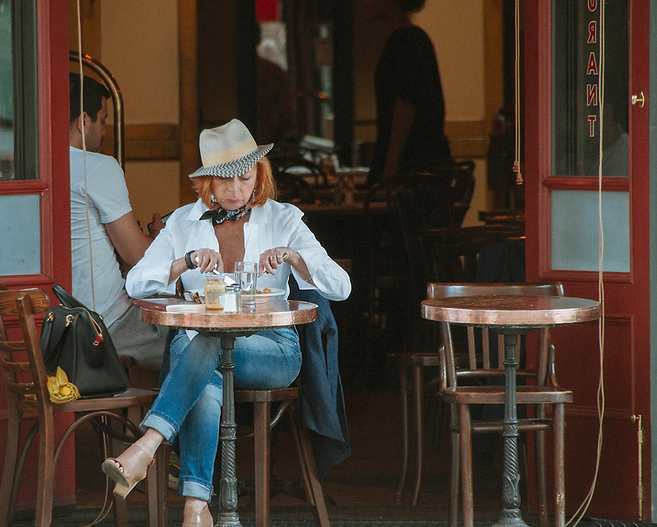 Stylish woman with cool hat and bandana enjoys her food at cafe'. NYC 2017