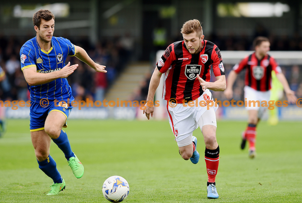 Tom Barkhuizen of Morecambe (right)  races against Jon Meades of Wimbledon for the ball during the Sky Bet League 2 match between AFC Wimbledon and Morecambe at the Cherry Red Records Stadium in Kingston. October 17, 2015.<br /> Simon  Dack / Telephoto Images<br /> +44 7967 642437
