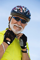 Portrait of Senior man adjusting cycling helmet