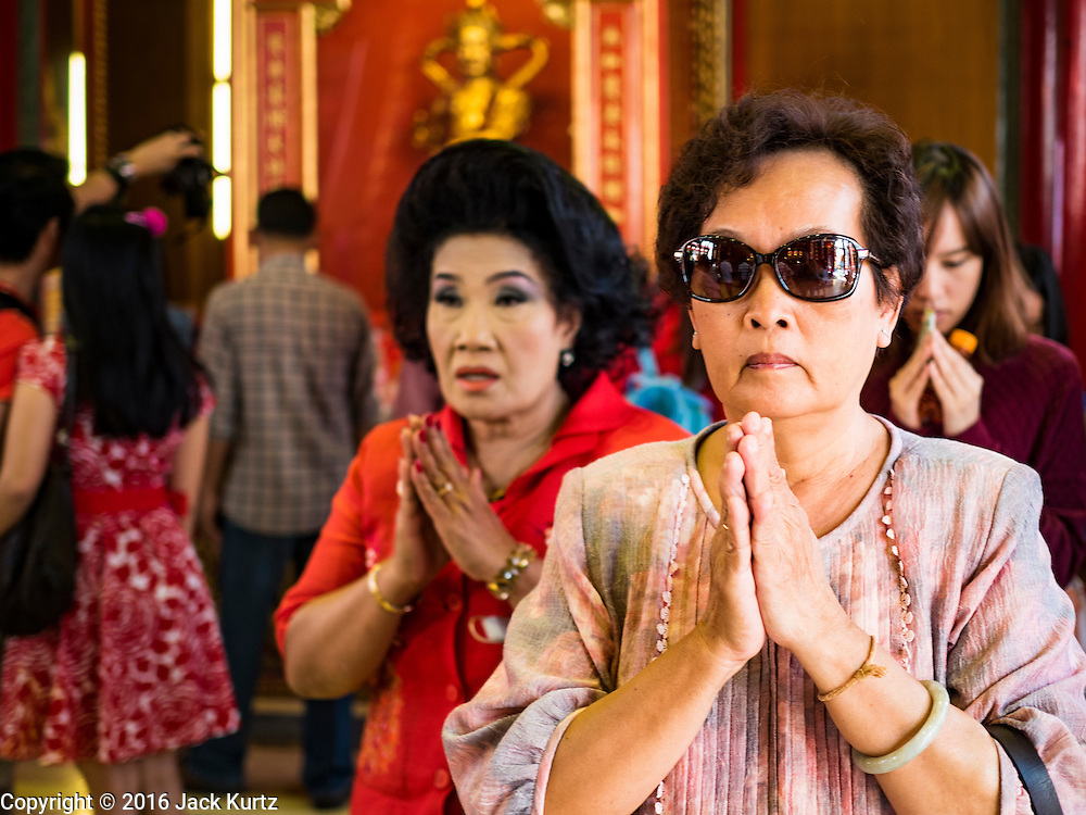 "07 FEBRUARY 2016 - BANGKOK, THAILAND: Women pray during Chinese New Year ceremonies at Wat Mangon Kamlawat in Bangkok. Chinese New Year, also called Lunar New Year or Tet (in Vietnamese communities) starts Monday February 8. The coming year will be the ""Year of the Monkey."" Thailand has the largest overseas Chinese population in the world; about 14 percent of Thais are of Chinese ancestry and some Chinese holidays, especially Chinese New Year, are widely celebrated in Thailand.        PHOTO BY JACK KURTZ"