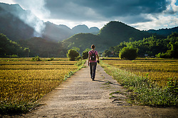 A woman walks on a deserted road, Mai Chau area, Hoa Binh Province, Vietnam, Southeast Asia