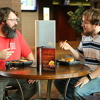 James Strachan and Corey Walker, both projector technicians at Malco, take a break on the commons area to eat a cheese burger meal that was cooked at the theater. Malco now offers hamburgers, fries, chicken tenders, pizza along with many other food items.