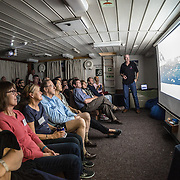 Passengers aboard the Polar Pioneer listen to a lecture on the geography of the Antarctic continent led by expedition leader Don McFadzien of Aurora Expeditions (standing, at right).