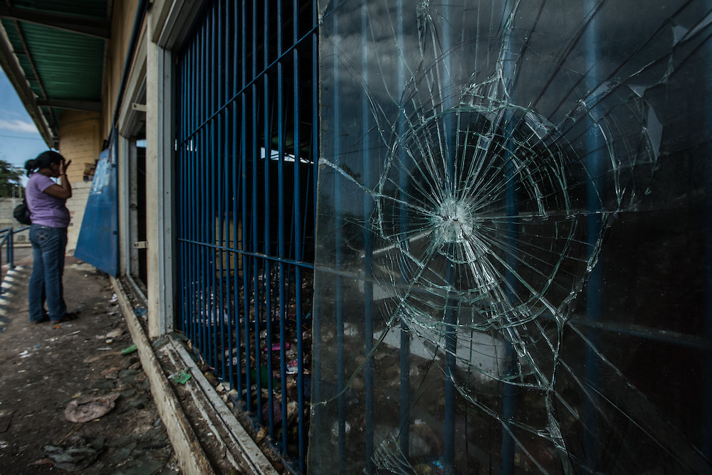 CUMANÁ, VENEZUELA - JUNE 16, 2016:  A broken window at a grocery store that was destroyed last Tuesday by hundreds of looters in Cumaná, Venezuela. They made it through the doors before the owners could close them, forced a large metal gate open so those outside could pour inside. They took water, flour, corn meal, salt, sugar, potatoes, cereal—leaving behind only a broken freezers and overturned shelves. And they proved that even in country with the richest oil reserves in the world, it was possible for people to riot because there was no food. Venezuela is convulsing from a raft of violence triggered by hunger. It is latest chapter of an economic collapse which has left the country neither able to produce its food nor import it from abroad, leaving a nation searching for how to feed itself. In the past 11 days, scores of businesses, mostly stores, have been looted or destroyed and five people have died in the confrontations. With delivery trucks under constant attack, the nation's food is now transported under armed guard. Entire cities have been militarized under an emergency decree from President Nicolás Maduro; bakeries are now watched over by the National Guard.  PHOTO: Meridith Kohut for The New York Times
