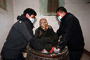 QUANZHOU, CHINA - JANUARY 10: (CHINA OUT) <br /> <br /> Workers open the vat in which monk Fuhou\'s body has been put for three and a half years at Puzhao temple on Zimao Mountain on January 10, 2016 in Quanzhou, Fujian Province of China. 94-year-old monk Fuhou died in 2012 and his body was put by the sitting position into a vat with a cover for three and a half years. Monks found that Fuhou\'s body wasn\'t rotted on an opening vat rite on January 10 at Puzhao temple on Zimao Mountain in Quanzhou. The body would be cleaned and stuck with gold to be made into a golden Buddha.<br /> ©Exclusivepix Media
