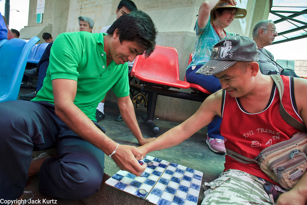 Mar. 8, 2009 -- BANGKOK, THAILAND: Men play checkers in the Chatuchak Weekend Market. The market covers an area of 35 acres with more than 15,000 shops and stalls. It has over 200,000 visitors each day it's open (Friday - Sunday), and they spend an estimated total of 30 million baht (approx US$750,000). The range of products on sale is extensive, and includes household accessories, handicrafts, religious artifacts, art, antiques, live animals (which unfortunately are frequently caged in cruel conditions), books, music, clothes, food, plants and flowers. Photo by Jack Kurtz / ZUMA Press