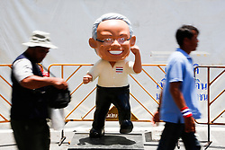 © Licensed to London News Pictures. 15/05/2014. PDRC protestors walk past a cartoon statue of PDRC leader Suthep Thaugsuban at a protest site near the site of a grenade and gun shots attack at Democracy monument in Bangkok on May 15, 2014. Grenade blasts and gunfire rocked an anti-government protest site in Thailand's capital, leaving two dead and 24 wounded as fears of wider political violence mounted in Bangkok Thailand. Photo credit : Asanka Brendon Ratnayake/LNP