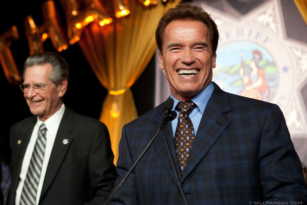"""California Governor Arnold Schwarzenegger speaks at the retirement party honoring San Diego Sheriff Bill Kolender, Oct. 05, 2009. At one point Schwarzenegger pinched Kolender's cheek and joked, """"He did the security for Moses."""""""