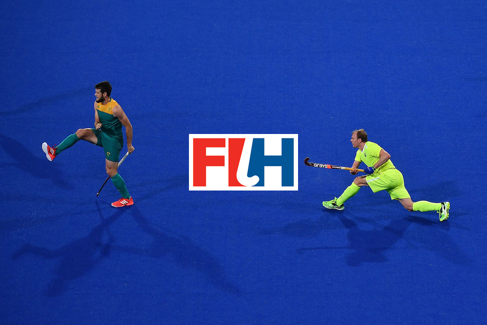 Australia's Matt Gohdes (L) and Brazil's Ernst Rost vie during the mens's field hockey Australia vs Brazil match of the Rio 2016 Olympics Games at the Olympic Hockey Centre in Rio de Janeiro on August, 12 2016. / AFP / MANAN VATSYAYANA        (Photo credit should read MANAN VATSYAYANA/AFP/Getty Images)