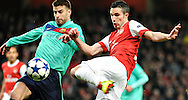 Arsenal's Robin Van Persie, right, challenges for the ball with Barcelona's Gerard Pique during a Champions League, round of 16, first leg soccer match at Arsenal's Emirates stadium in London, Wednesday, Feb., 16, 2011