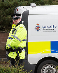 © Licensed to London News Pictures . 11/02/2014 . Blackburn , UK . A police officer at the scene . Police and forensic examiners on Emily Street in Blackburn at the scene where an eleven month old baby girl was mauled to death late last night (10th February 2014) . Photo credit : Joel Goodman/LNP