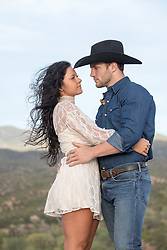 cowboy and a girl outdoors embracing