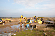 Heavy machinery used to build coastal defence against rapid erosion at East Lane, Bawdsey, Suffolk, England, UK