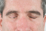 close up of a middle aged man's face with his eyes relaxed closed