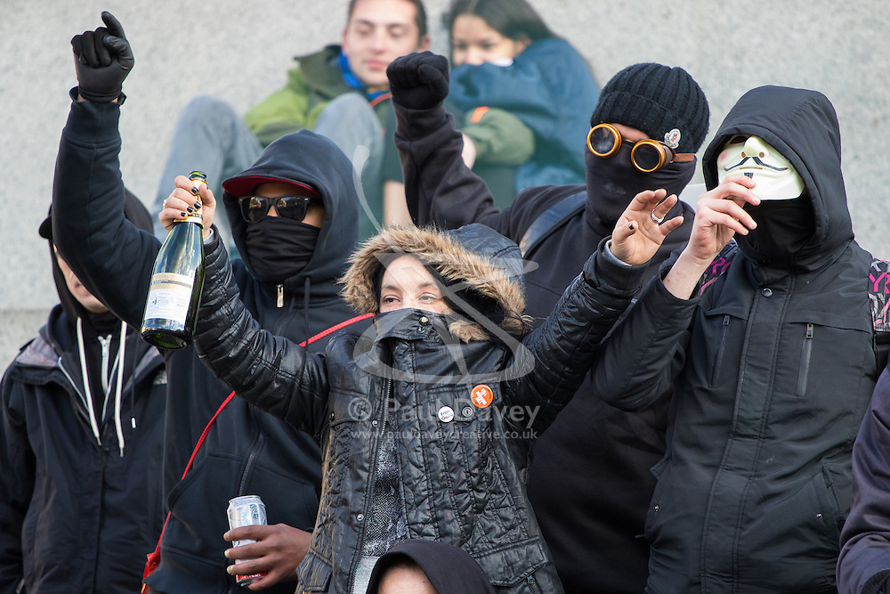 """London, April 16th 2016. A young woman clutches a bottle of cava as anarchists let off a smoke bomb on the plinth of Nelson's column in Trafalgar Square after thousands of people supported by trade unions and other rights organisations demonstrated against the policies of the Tory government, including austerity and perceived favouring of """"the rich"""" over """"the poor""""."""