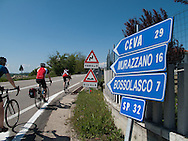A group of cyclists riding by directional signs in the Piedmont region of northern Italy. http://www.gettyimages.com/detail/photo/cyclists-pass-by-directional-road-signs-royalty-free-image/120983430