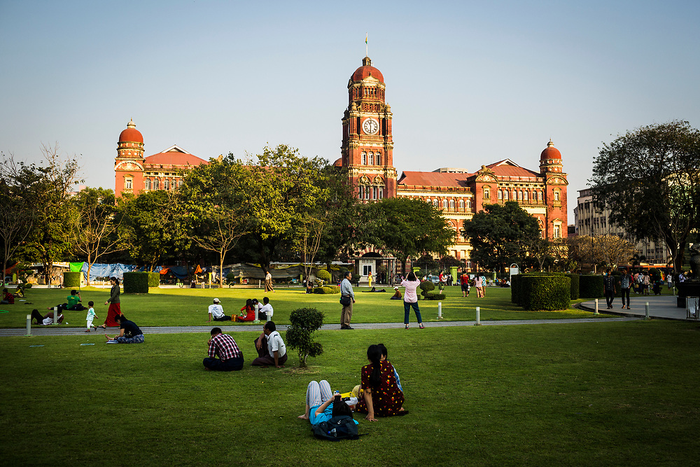People sit in the Maha Bandoola Gardens with an old colonial building in the background in Yangon, Myanmar.