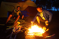 Campfire sparks fly was two guys enjoy good company around a summer camp in Hawaii