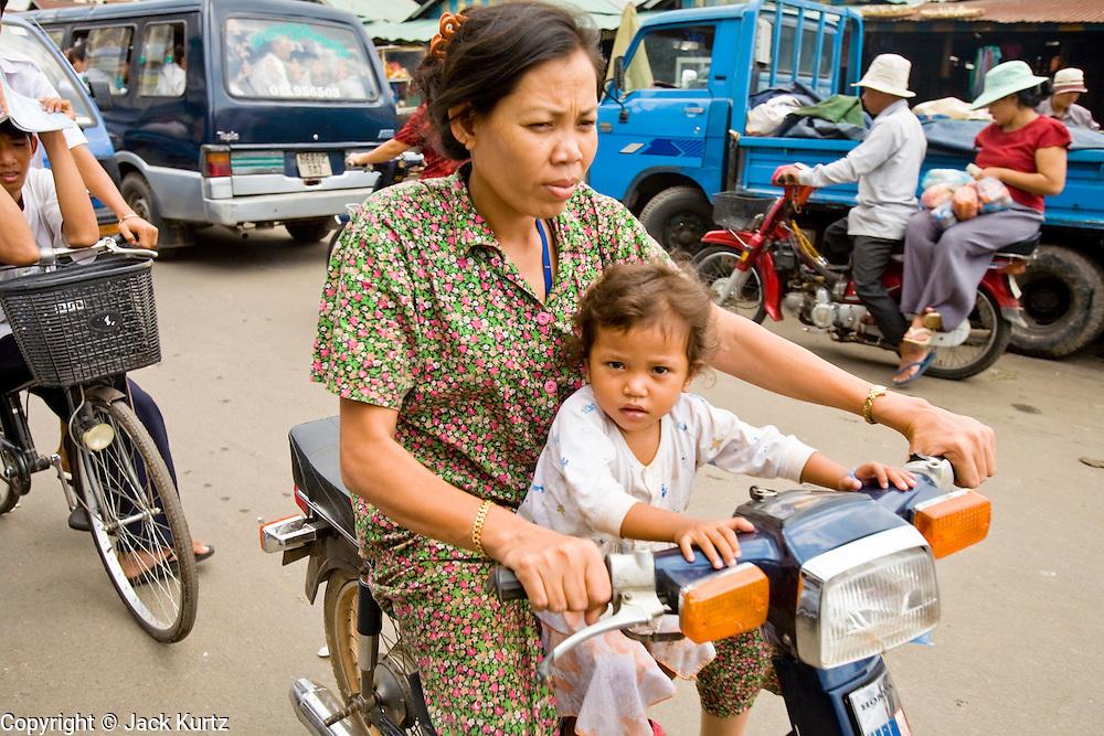 14 MARCH 2006 - PHNOM PENH, CAMBODIA: Motor scooter and cyclo traffic in Phnom Penh, Cambodia. PHOTO BY JACK KURTZ