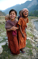 "RUKUM DISTRICT, NEPAL, APRIL 15, 2004:  Children carry their siblings in a small village in Rukum District April 15, 2004. Ill-equipped security forces in politically unstable Nepal are unable to control  Maoist rebels, who continue to abduct thousands of villagers for forcible indoctrination and military training.  The Maoists mainly target students, teachers and youths. The victims are usually released after a few days of indoctrination, unless they actively resist the ""training attempts,"" in which case the rebels torture or sometimes kill them. Maoist insurgents have capture most of the Western part of Nepal in their attempt to make it a Communist State. Analysts and diplomats estimate there about 15,000-20,000 hard-core Maoist fighters, including many women, backed by 50,000 ""militia"".  In their remote strongholds, they collect taxes and have set up civil administrations, and people's courts. They also raise money by taxing villagers and foreign trekkers.  They are tough in Nepal's rugged terrain, full of thick forests and deep ravines and the 150,000 government soldiers are not enough to combat this growing movement that models itself after the Shining Path of Peru. (Ami Vitale/Getty Images)"
