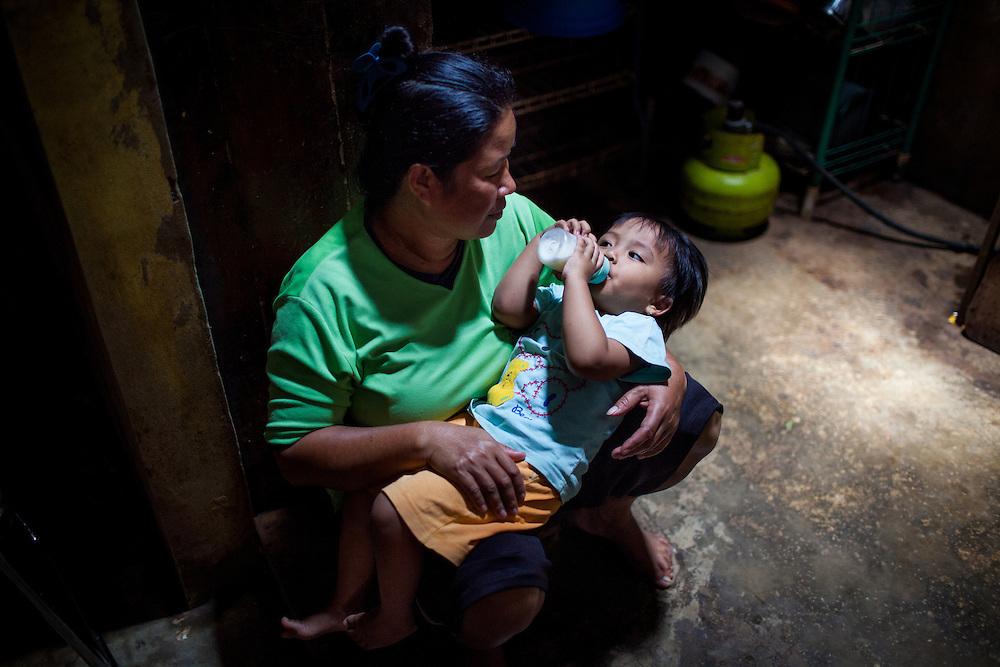 Karwati, Abah Dayat's wife, looks after her granddaughter, Aulia (2).  Citeureup Village, Kabupaten Bandung...Credit: Andri Tambunan for Greenpeace