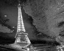 The iconic Eiffel Tower in Paris as reflected on a rain-slicked street. Seen here in black and white.