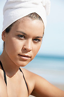Young woman with hair wrapped in towel on beach close-up