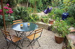 General view of small town garden. Gravelled patio area with table and chairs, paved area beyond